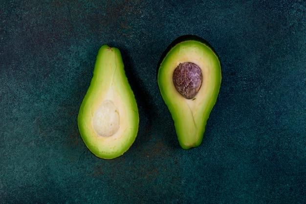 Вид сверху разрезать пополам авокадо на темно-зеленом фоне