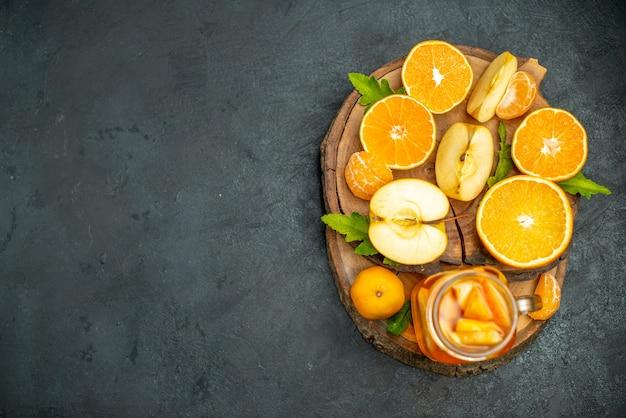 상위 뷰는 오렌지를 자르고 사과는 어두운 배경에서 오렌지를 자릅니다.