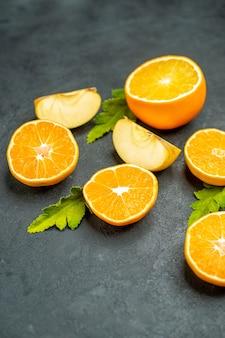 상위 뷰는 어두운 표면에 오렌지와 사과를 잘라냅니다.