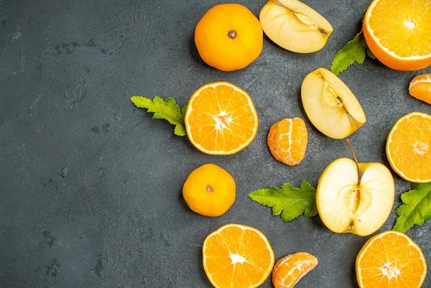 Вид сверху нарезанные апельсины и яблоки на темной поверхности