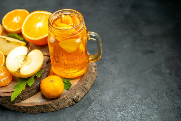 Vista dall'alto tagliare le arance e le mele tagliate l'arancia su sfondo scuro