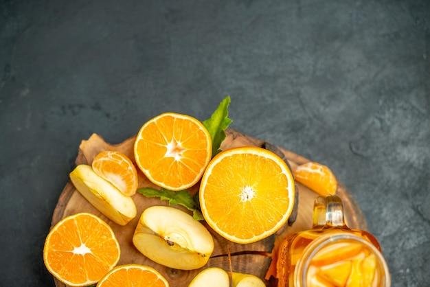 Vista dall'alto tagliare le arance e le mele tagliate l'arancia su una superficie scura