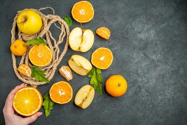 La vista dall'alto taglia le arance e le mele tagliano l'arancia in mano femminile su una superficie scura