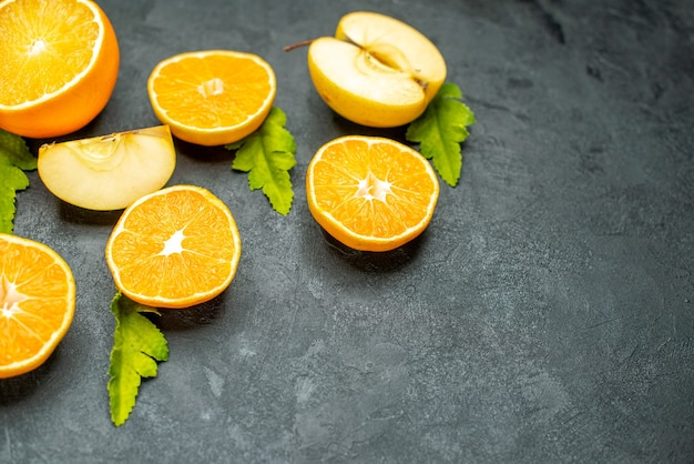 Vista dall'alto tagliare arance e mele su sfondo scuro
