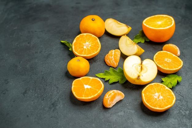 Vista dall'alto tagliare arance e mele su una superficie scura