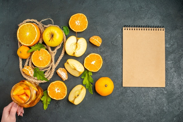 Top view cut oranges and apples notepad cocktail in female hand on dark background