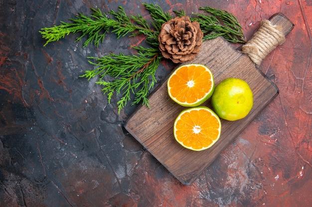 상위 뷰는 진한 빨간색 표면 여유 공간에 콘으로 보드 소나무 나뭇 가지를 자르고 오렌지를 잘라