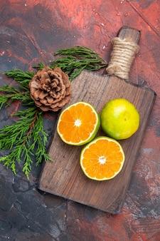 상위 뷰는 진한 빨간색 표면에 콘으로 보드 소나무 나무 가지를 자르고 오렌지를 잘라