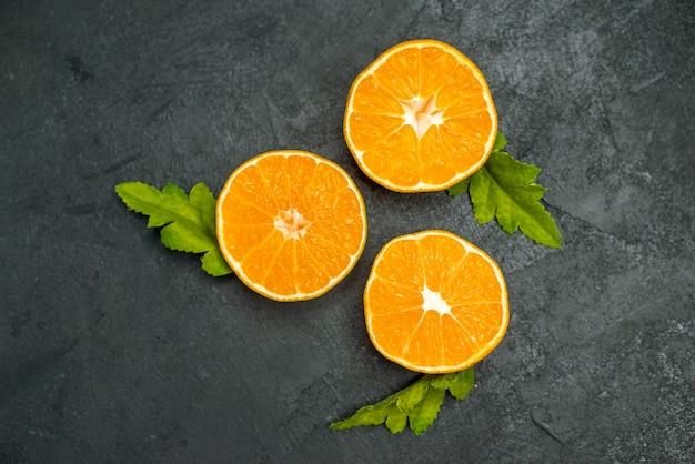 Вид сверху нарезанные апельсины на темном фоне
