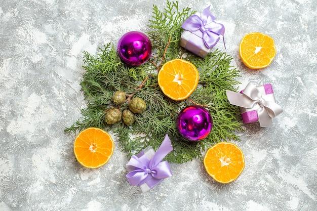 상위 뷰 컷 오렌지 소나무 나무 가지 크리스마스 트리 장난감 회색 배경에 작은 선물