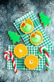Vista dall'alto tagliate le arance albero di natale caramelle piccole crostate su asciugamano da cucina a scacchi bianco verde sul tavolo grigio