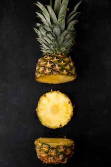Top view of cut pineapple on black surface