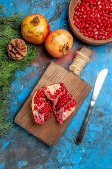Vista dall'alto un melograno tagliato sul tagliere coltello da pranzo una ciotola di semi di melograno su sfondo blu