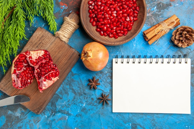 Top view a cut pomegranate and dinner knife on chopping board pomegranate seeds in bowl and pomegranates cinnamon anise seeds a notebook on blue background