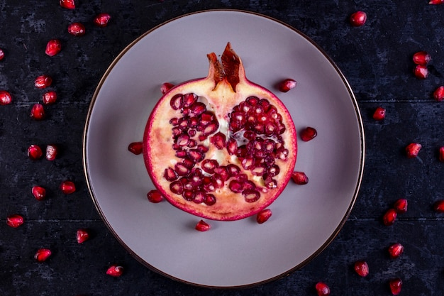 Top view cut pomegranate on a white plate  on a black table