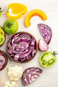 Вид сверху нарезанной красной капусты в деревянной миске зеленый помидор тыква красный лук болгарский перец цветная капуста лимон на белом фоне