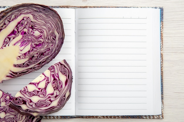 Top view cut red cabbage on open notebook on wooden table