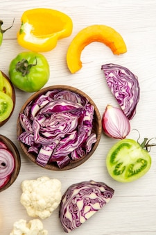 Top view cut red cabbage in wooden bowl green tomato pumpkin red onion bell pepper caulifower lemon on white ground