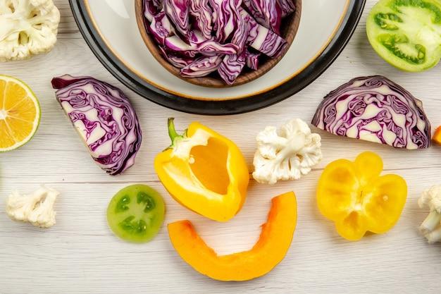 Vista dall'alto tagliare i cavoli rossi nella ciotola sul piatto rotondo tagliare le verdure sulla superficie bianca