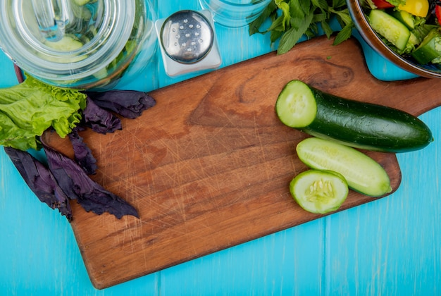 Top view of cut and sliced cucumber on cutting board with basil lettuce mint vegetable salad detox water and salt on blue surface