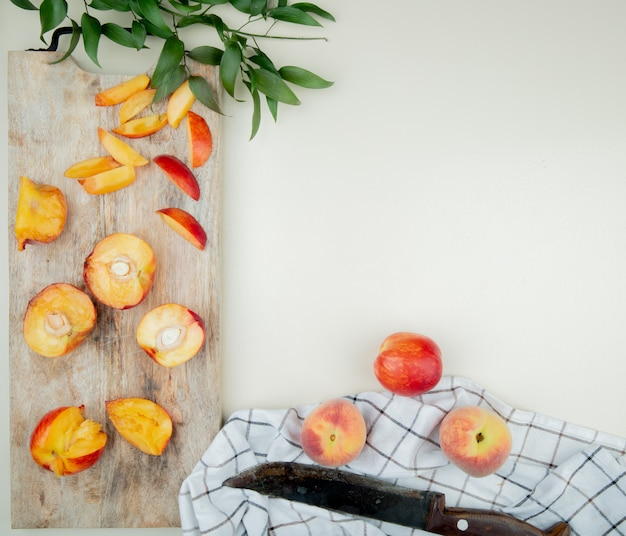 Top view of cut and sliced peaches on cutting board with whole peaches and knife on cloth on white surface decorated with leaves with copy space