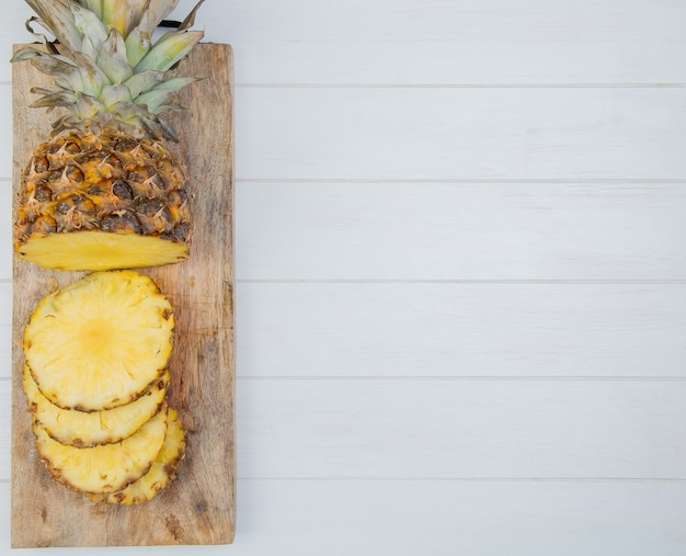 Top view of cut and sliced pineapple on cutting board on left side and wooden background with copy space