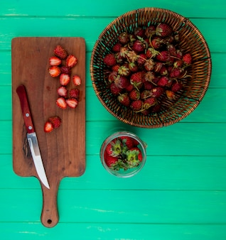 Top view of cut strawberries with knife on cutting board and whole strawberries in basket and bowl on green surface