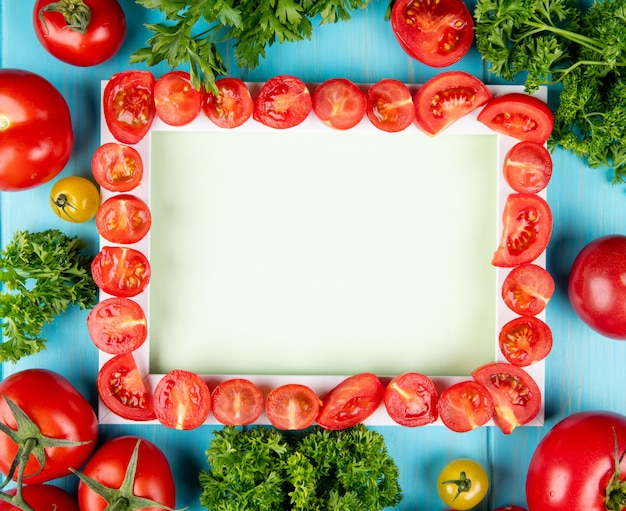 Top view of cut tomatoes on board with other ones and coriander on blue surface with copy space