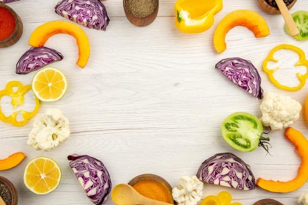 上面図カット野菜カリフラワーカットピーマンカットカボチャカット赤キャベツカットグリーントマト白い木製テーブルの空きスペース
