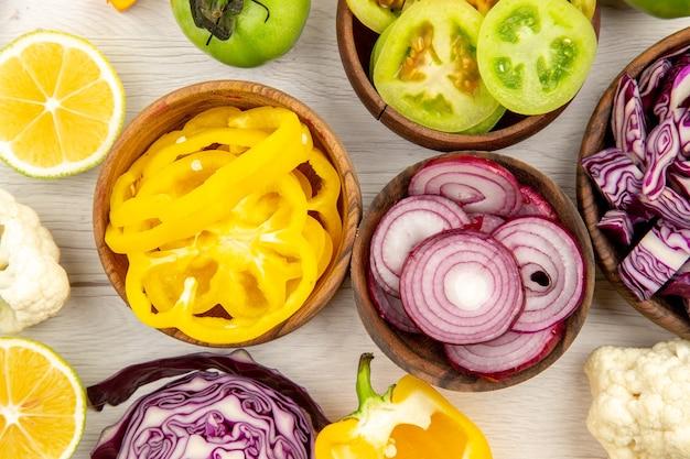 상위 뷰 잘라 야채 붉은 양배추 녹색 토마토 호박 붉은 양파 피망 caulifower 레몬 흰색 바닥에 나무 그릇에