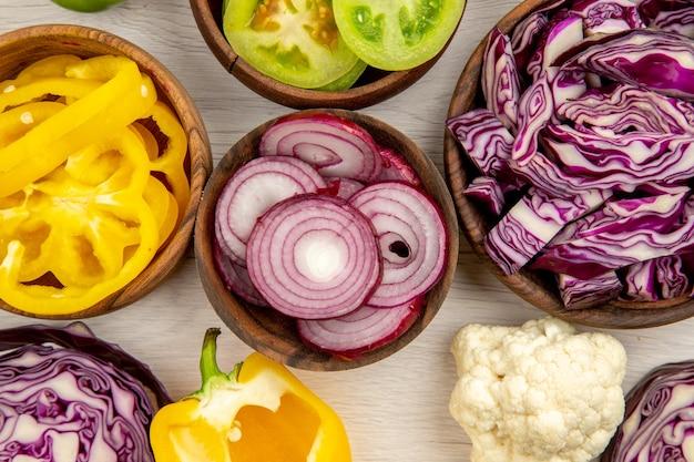 Вид сверху нарезанные овощи красная капуста зеленый помидор тыква красный лук болгарский перец цветная капуста лимон в деревянных мисках на белой деревянной поверхности