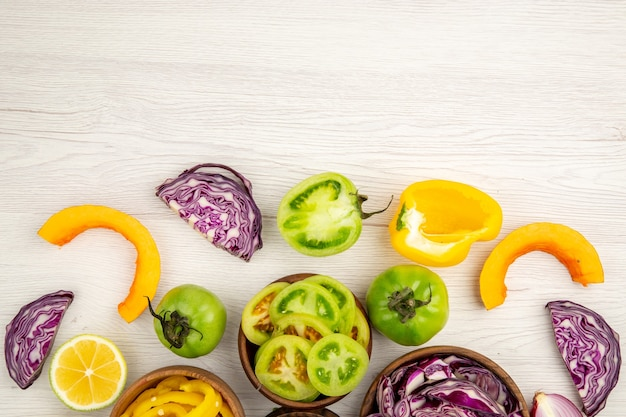Top view cut vegetables red cabbage green tomato pumpkin red onion bell pepper caulifower lemon in wooden bowls on ground free place
