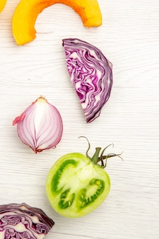 Top view cut vegetables red cabbage green tomato pumpkin red onion on white surface