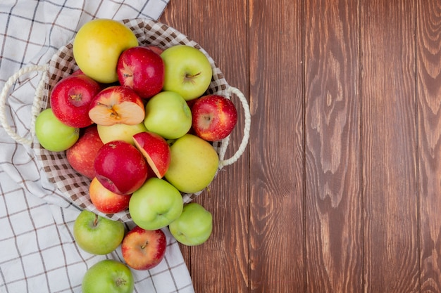 Top view of cut and whole apples in basket and on plaid cloth on wooden background with copy space