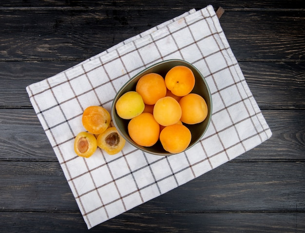 Top view of cut and whole apricots on cloth and wooden table