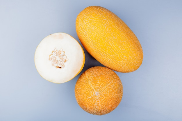 Top view of cut and whole melons on bluish gray background
