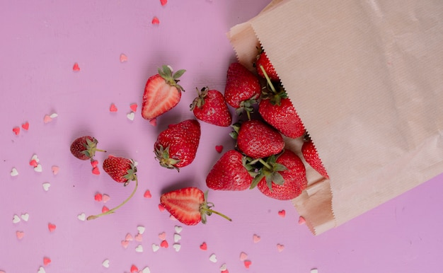 Top view of cut and whole strawberries spilling out of paper bag on purple table
