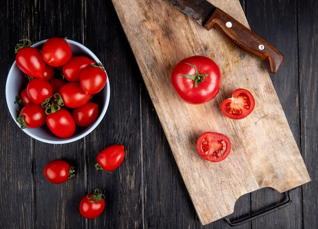 Top view of cut and whole tomatoes and knife on cutting board with other ones in bowl on wooden surface