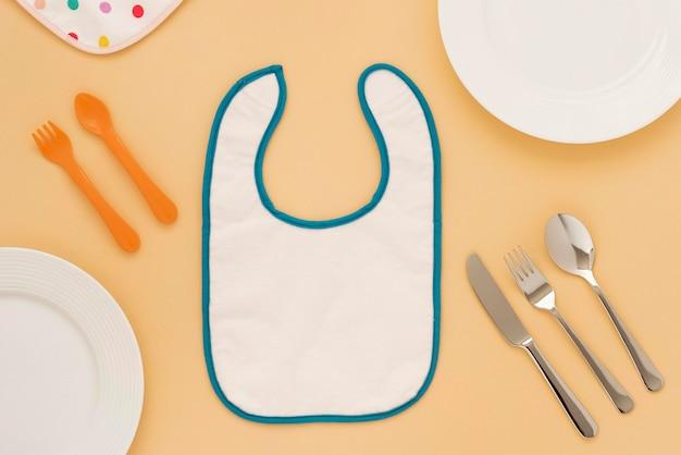 Вид сверху милые детские нагрудники и посуда
