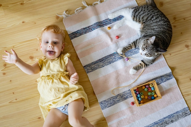 Top view cute baby girl in dress having fun lying on floor with cat playing wooden removable beads