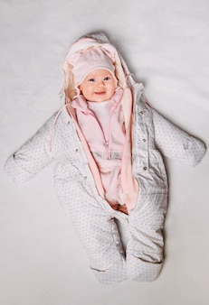 Top view of a cute baby in a white and pink clothes on snow