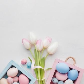 Vista dall'alto di scatole carine con uova colorate di pasqua e bouquet di tulipani
