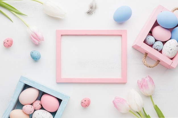 Top view of cute boxes with colorful easter eggs and frame