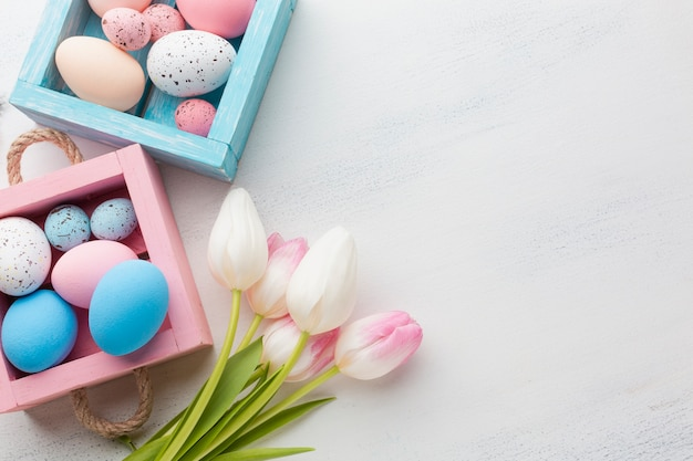 Top view of cute boxes with colorful easter eggs and tulips