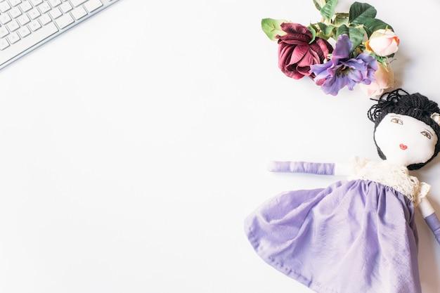 Vista dall'alto di una bambola carina con fiori su una superficie bianca con una tastiera su di essa
