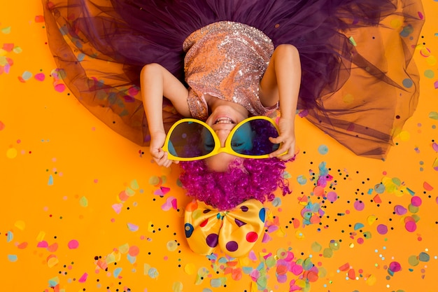 Top view of cute girl with clown wig and big sunglasses