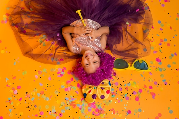 Top view of cute girl with clown wig and confetti