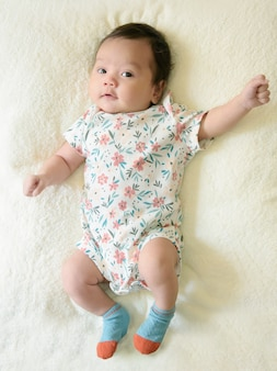 Top view of cute little asian baby girl, wearing a pretty floral dress, lying on white bed and looking at the camera