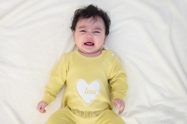 Top view of a cute little asian baby girl wearing yellow dress, lying on the bed, sad and crying