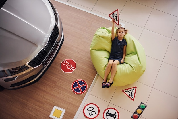 Top view of cute little girl that holds road signs in hands in automobile salon.